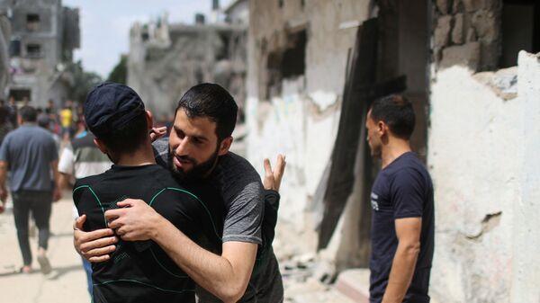 Палестинцы обнимаются друг с другом после возвращения в свои разрушенные дома после перемирия между Израилем и ХАМАС в Бейт-Хануне  - Sputnik Mundo