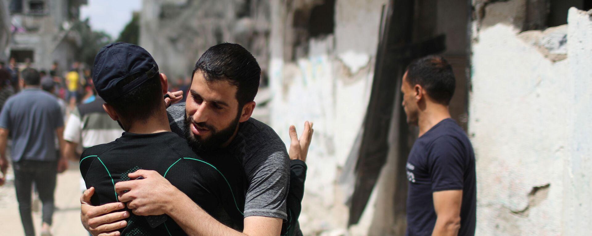 Палестинцы обнимаются друг с другом после возвращения в свои разрушенные дома после перемирия между Израилем и ХАМАС в Бейт-Хануне  - Sputnik Mundo, 1920, 21.05.2021
