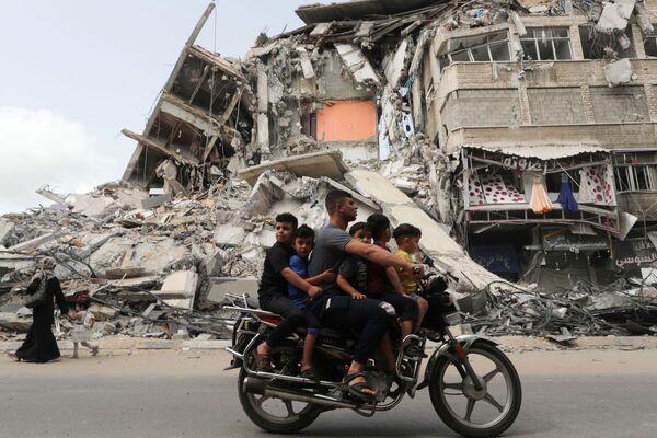 Unos palestinos pasan por el lugar de uno de los ataques aéreos israelíes en Gaza. - Sputnik Mundo