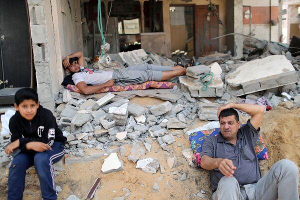 Unos palestinos en su casa destruida por un misil, en Beit Hanun, al noreste de Gaza. - Sputnik Mundo