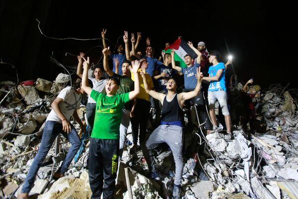 Unos palestinos celebran el cese al fuego en Gaza. - Sputnik Mundo