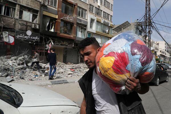 El 20 de mayo, el gabinete de seguridad del primer ministro de Israel, Benjamin Netanyahu, aprobó un alto el fuego unilateral. En la foto: un palestino pasa frente a unos edificios bombardeados por Israel. - Sputnik Mundo