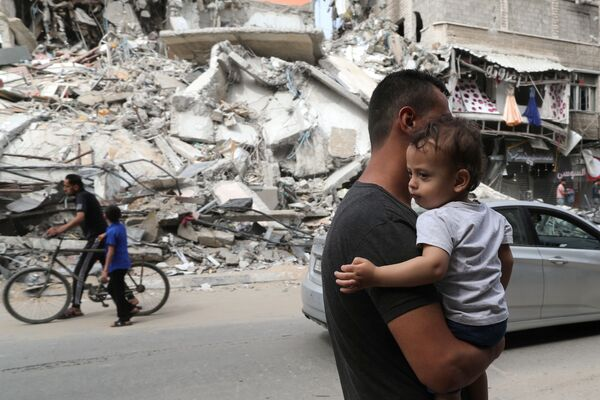 Unos palestinos pasan por unos edificios destruidos durante el conflicto entre Israel y Hamás. - Sputnik Mundo