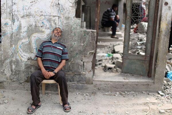 Desde el inicio del conflicto, las facciones radicales palestinas atacaron el territorio de Israel con 4.070 misiles, lo que dejó más de 50 heridos y 12 víctimas mortales. En Palestina, 230 personas fallecieron y 1.710 resultaron heridas a raíz de los ataques aéreos israelíes. En la foto: un palestino se relaja en su casa destruida, en Beit Hanun, al noreste de Gaza. - Sputnik Mundo