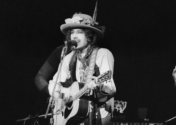 """A finales de 1963, Dylan sintió que se había convertido en un prisionero de su propia imagen. En 1965, dejó en shock a los aficionados al folk acústico al tocar la guitarra eléctrica en el Newport Folk Festival, algo que entró en la historia de la música como """"la controversia eléctrica de Bob Dylan"""". En la foto: un concierto de Bob Dylan en el Madison Square Garden, en 1975. - Sputnik Mundo"""