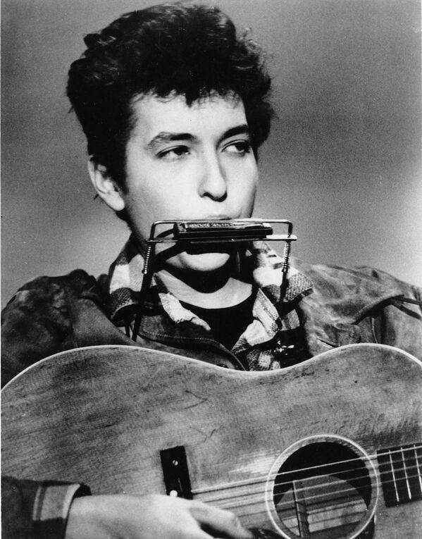 Al igual que otros adolescentes de su generación, el joven Bob Dylan era un gran aficionado al rock'n'roll y tocó 'covers' de los éxitos de Elvis Presley y Little Richard junto a los compañeros de su grupo musical que formó en el colegio. En la foto: Bob Dylan toca la armónica y la guitarra en un club de EEUU, en 1963. - Sputnik Mundo