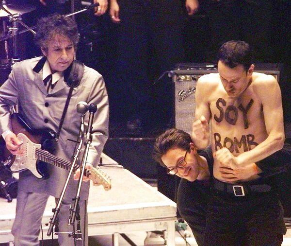 A principios de la década de 1990, Dylan dejó de componer canciones durante varios años luego de que su 27 álbum, titulado 'Under the Red Sky', fracasara. En 1998, el artista regresó a la música y hasta se llevó tres estatuillas Grammy. En la foto: el artista Michael Portnoy con las palabras 'Bomba de soja' escritas en su torso sube al escenario durante la actuación de Dylan como parte de una 'performance'. - Sputnik Mundo