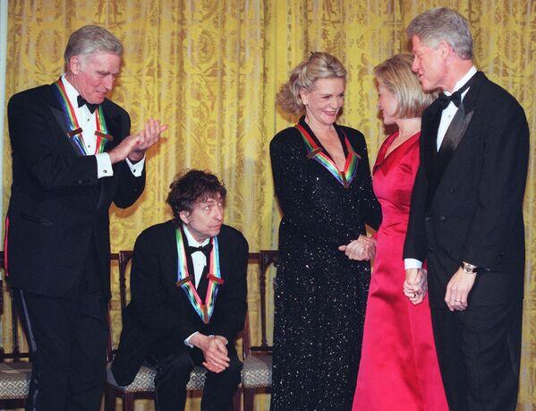 La discografía de Bob Dylan cuenta con casi 40 álbumes de estudio. En 2020, el cantautor lanzó el disco 'Rough and Rowdy Ways' que incluyó la balada 'Murder Most Foul' en la que reflexiona sobre las consecuencias que tuvo el asesinato de John F. Kennedy. En la foto: Bob Dylan en la gala de los premios del Centro Kennedy en la Casa Blanca, en 1997. A la derecha, Hillary y Bill Clinton. - Sputnik Mundo