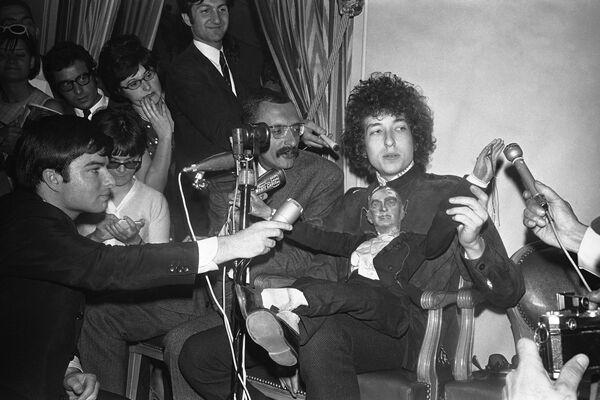 Dylan saltó a la fama a principios de la década de 1960. Tras abandonar la universidad en su natal Minnesota, se mudó a Nueva York, donde pronto se convirtió en un popular cantante de folk. Fue el crítico Robert Shelton quien vio una de las actuaciones de Dylan y lo invitó a colaborar con la discográfica Columbia Records. En la foto: Bob Dylan en una conferencia de prensa celebrada en el hotel George V, en París, en 1966. - Sputnik Mundo