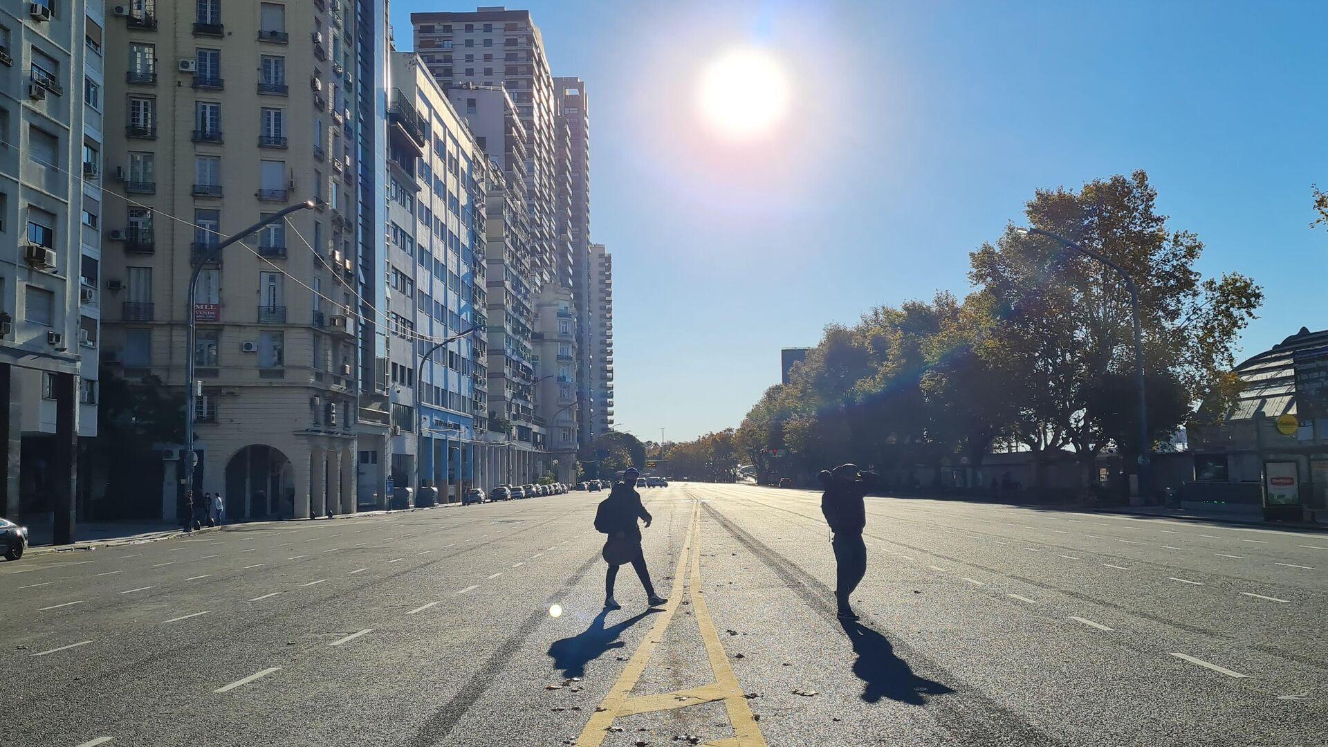 Dos personas cruzan una calle casi desierta Buenos Aires durante el feriado del 25 de mayo - Sputnik Mundo, 1920, 25.05.2021