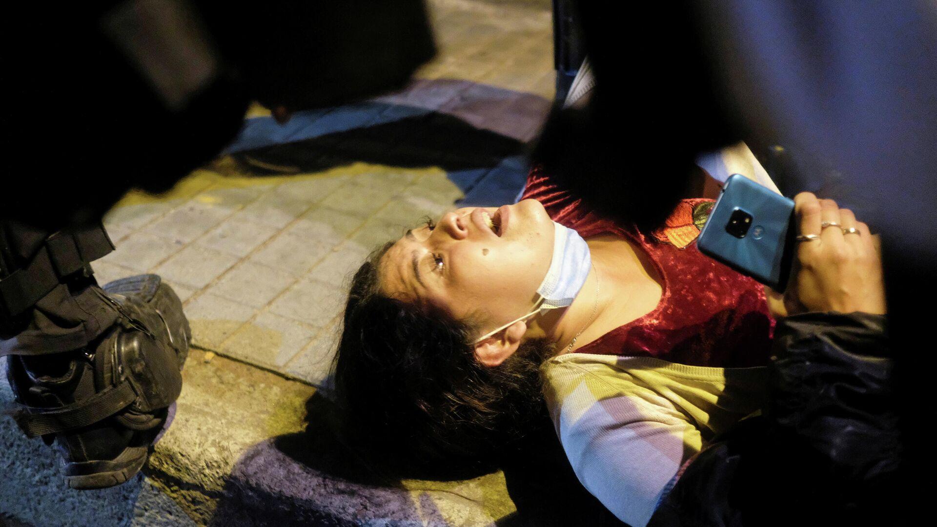 Una manifestante se cayó al suelo durante las protestas en Bogotá - Sputnik Mundo, 1920, 27.05.2021