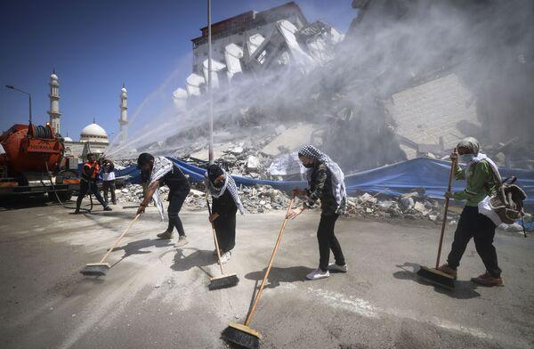 Unos funcionarios municipales y unos voluntarios palestinos limpian los escombros en la ciudad de Gaza tras unos ataques aéreos israelíes. - Sputnik Mundo