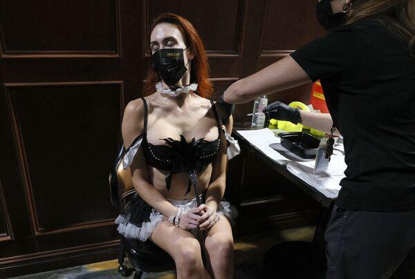 Una integrante del espectáculo Sexxy After Dark by Jennifer Romas recibe una vacuna contra el coronavirus en un sitio de vacunación temporal en el club de striptease Hustler Club en Las Vegas, Estados Unidos. - Sputnik Mundo