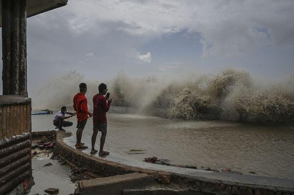 Unos lugareños fotografían las olas rompiendo a lo largo de la costa del golfo de Bengala en Digha, la India, durante el paso del ciclón Yaas por la región. - Sputnik Mundo