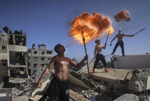 Unos miembros del equipo palestino Bar Woolf de Gaza realizan un espectáculo de fuego en las ruinas de un edificio destruido por los ataques aéreos israelíes. - Sputnik Mundo