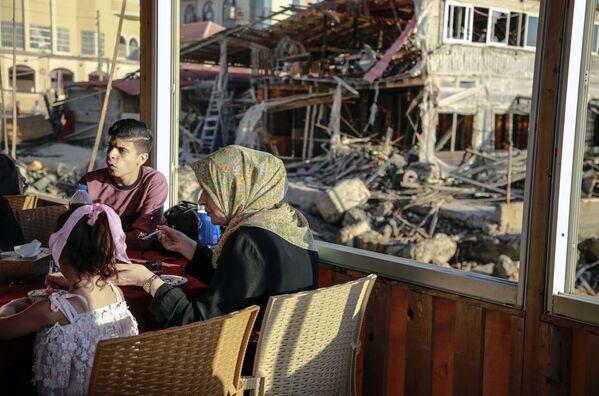 Unos palestinos vuelven a su casa destruida en la Franja de Gaza después del final del bombardeo israelí. - Sputnik Mundo
