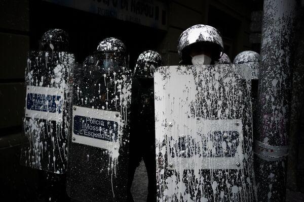 Unos agentes de la policía antidisturbios cubiertos con pintura arrojada por manifestantes montan guardia mientras los activistas intentan evitar el desalojo de un hombre de un apartamento en Barcelona, España. - Sputnik Mundo