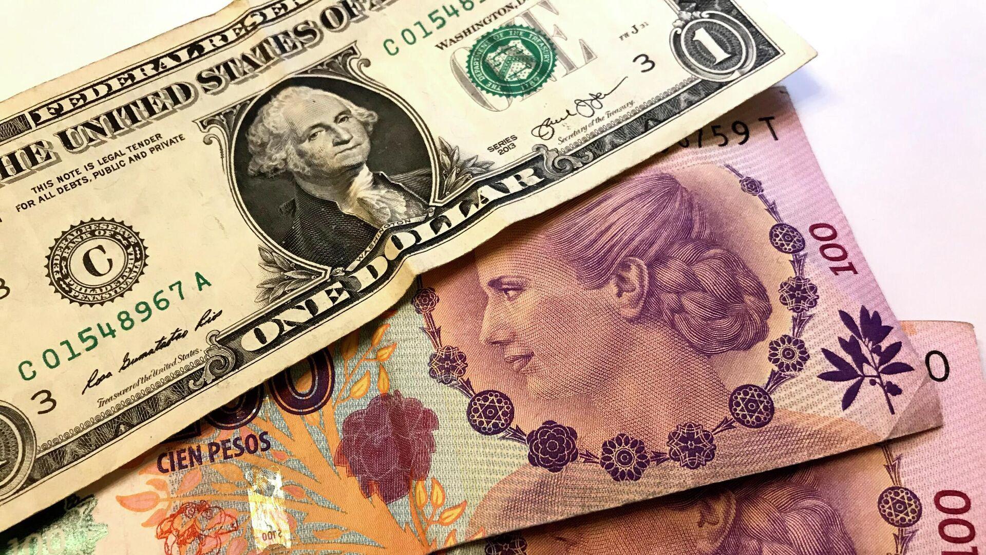 Pesos argentinos y un billete de dólar - Sputnik Mundo, 1920, 21.07.2021