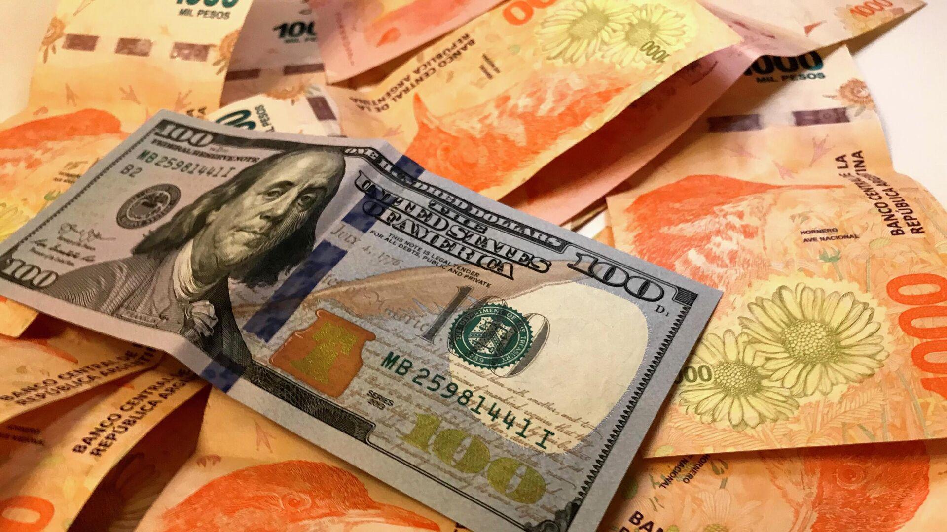 Pesos argentinos y un billete de dólar - Sputnik Mundo, 1920, 20.08.2021