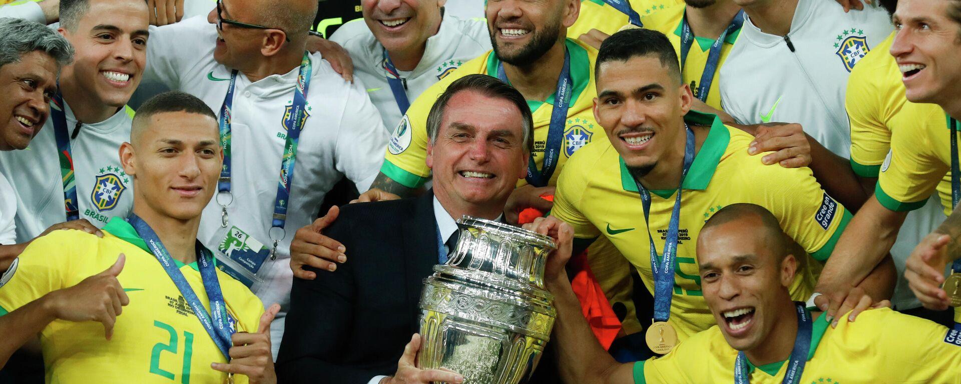El presidente de Brasil, Jair Bolsonaro, sostiene el trofeo de la Copa América 2019, ganada por la selección brasileña - Sputnik Mundo, 1920, 31.05.2021