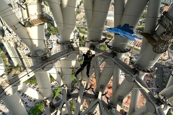 En esta torre puedes caminar sobre una cuerda con arnés, superar una carrera de obstáculos y subir hasta arriba. Y todo ello a una altura de casi 300 m sobre el suelo. En la foto: un guía camina sobre ella. - Sputnik Mundo