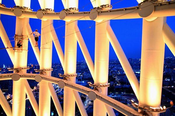 Esta torre de telecomunicaciones figura en la lista de los lugares y atracciones turísticas más importantes de China. En la foto, un guía y un visitante sobre la cuerda de la torre. - Sputnik Mundo