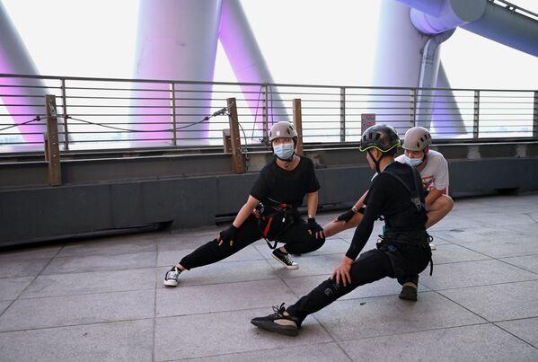 Quienes visitan la torre hacen ejercicios de estiramiento. - Sputnik Mundo