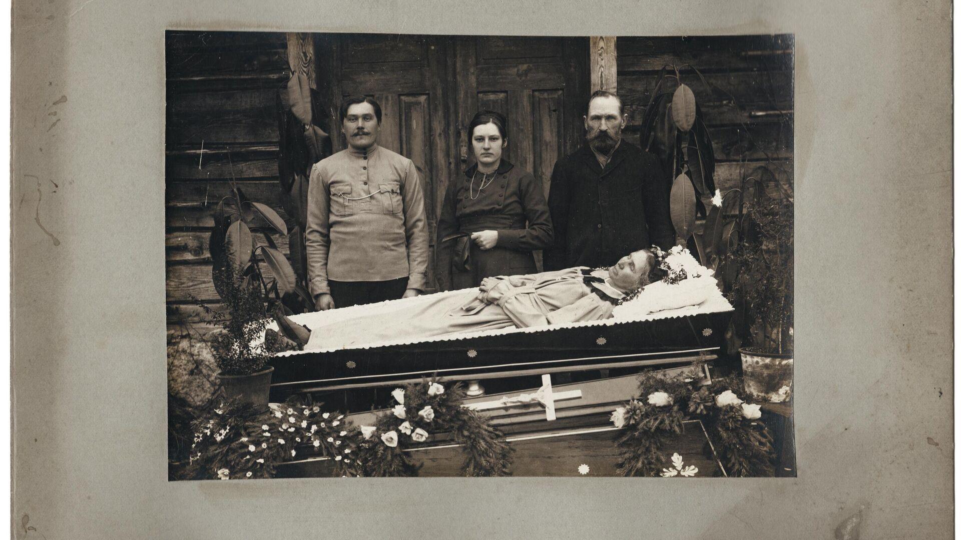 Familia velando el cuerpo sin vida de un ser querido - Sputnik Mundo, 1920, 02.06.2021
