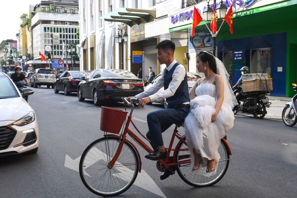 Una pareja de novios recorren la capital vietnamita de Hanói montada en una bicicleta.  - Sputnik Mundo