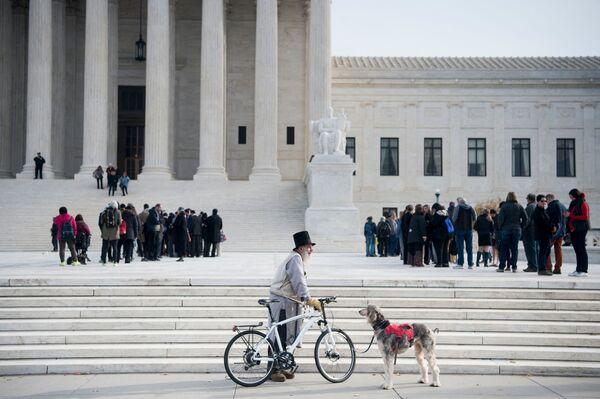 Un hombre estaciona su bicicleta frente al palacio de justicia en Washington, EEUU.  - Sputnik Mundo