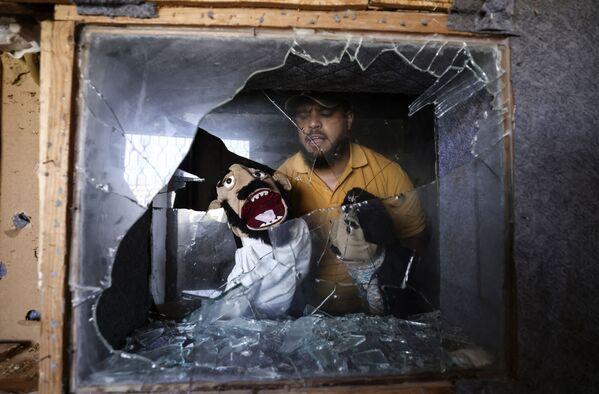 Mohammed Saed, un comediante palestino, muestra títeres que rescató de su estudio, dañado durante un reciente bombardeo israelí en Gaza (Palestina). - Sputnik Mundo