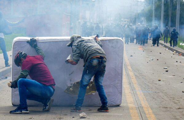 Unos manifestantes se protegen detrás de un colchón durante los enfrentamientos con la policía antidisturbios que estallaron durante una protesta contra el Gobierno del presidente colombiano Iván Duque, en Facatativá (Colombia). - Sputnik Mundo