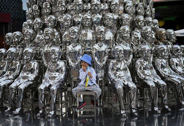Un niño posa entre unas esculturas en exhibición en un centro comercial en Pekín (China). - Sputnik Mundo
