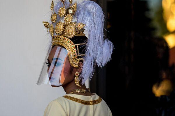 Una bailarina tradicional tailandesa con un protector facial se prepara para actuar durante un evento en el Museo Nacional de Bangkok (Tailandia). - Sputnik Mundo