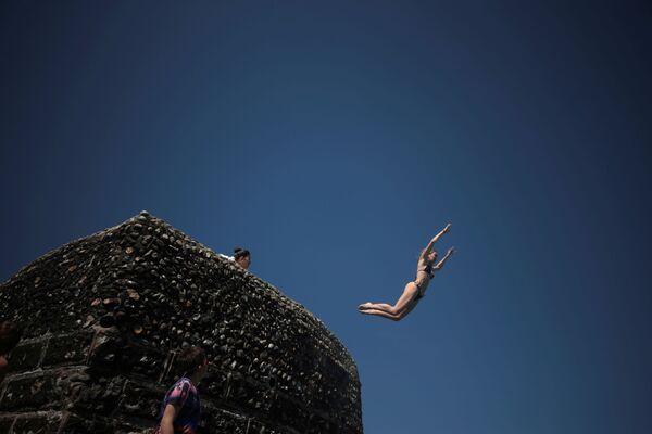 Una persona salta al mar en la playa de Brighton (Reino Unido). - Sputnik Mundo