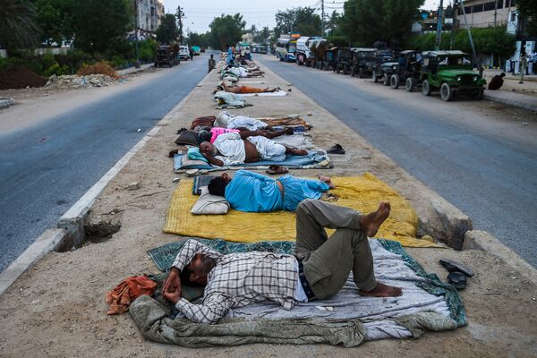 Unos trabajadores duermen en un divisor de carreteras en la ciudad portuaria de Karachi (Pakistán). - Sputnik Mundo