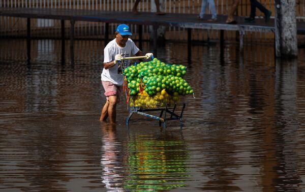 Un hombre lleva un carrito de frutas a lo largo de una calle inundada en el centro de Manaus (Brasil). - Sputnik Mundo