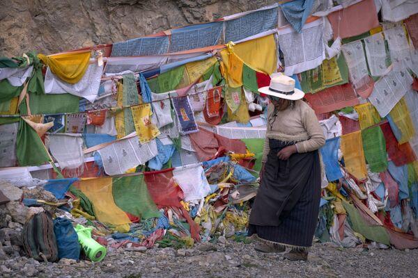 Una mujer tibetana pasa junto a banderas de oración en un santuario budista en Namtso, en la Región Autónoma del Tíbet (China). - Sputnik Mundo