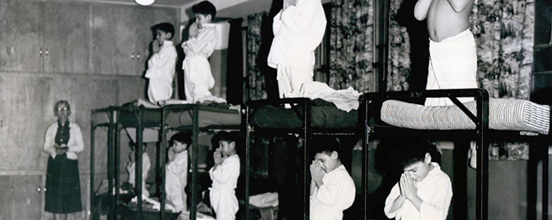 Мальчики молятся на кроватях в школе-интернате Bishop Horden в Канаде, 1950 год  - Sputnik Mundo, 1920, 07.06.2021