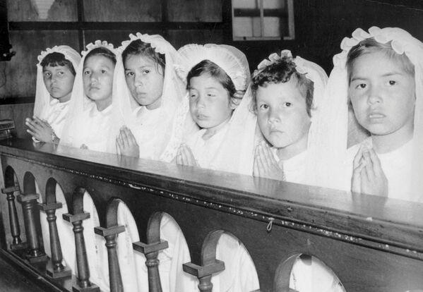 Los restos de 215 niños, la mitad de los cuales tenía 3 años, fueron hallados en la ciudad canadiense de Kamloops, la provincia de la Columbia Británica, en el sitio donde se situaba la antigua escuela residencial destinada a integrar a los niños indígenas.En la foto: las niñas durante la ceremonia de la primera comunión en una escuela residencial para los menores indígenas en la ciudad de Spanish, la provincia de Ontario, 1955.  - Sputnik Mundo