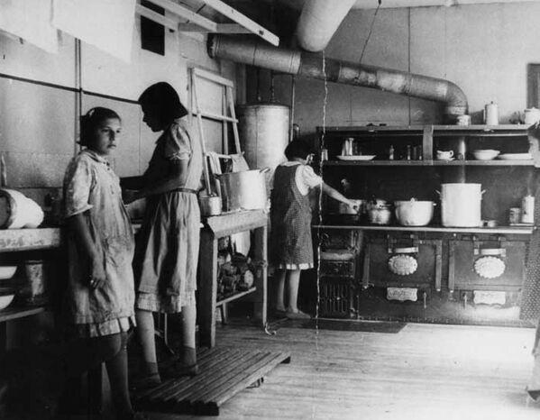 Se supone que mientras existieron las escuelas residenciales para menores indígenas murieron por lo menos 3.000 alumnos.En la foto: las niñas cocinan en la escuela residencial Bishop Horden, en 1940. - Sputnik Mundo