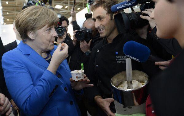 La canciller alemana, Angela Merkel, se come un helado mientras asiste a la feria Internationale Handwerksmesse en Munich (Alemania), en 2015. - Sputnik Mundo
