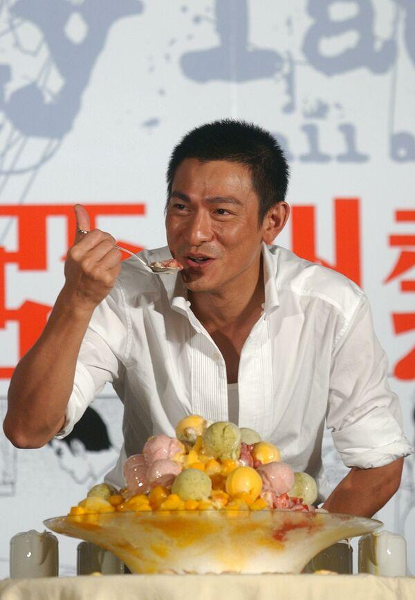 La historia del helado empezó hace unos 3.000 años en China, en donde se elaboraban refrescos con una mezcla de hielo, nieve y trozos de fruta.En la foto: el actor y cantante chino, Andy Lau, se come un helado durante una sesión fotográfica en Taipéi, en 2005. - Sputnik Mundo