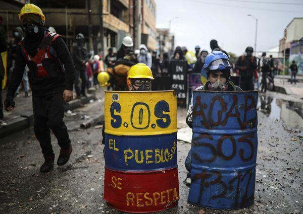 Los colombianos durante las protestas antigubernamentales se protegen de la policía con escudos artesanales, cascos y máscaras antigás en Bogotá, Colombia. - Sputnik Mundo