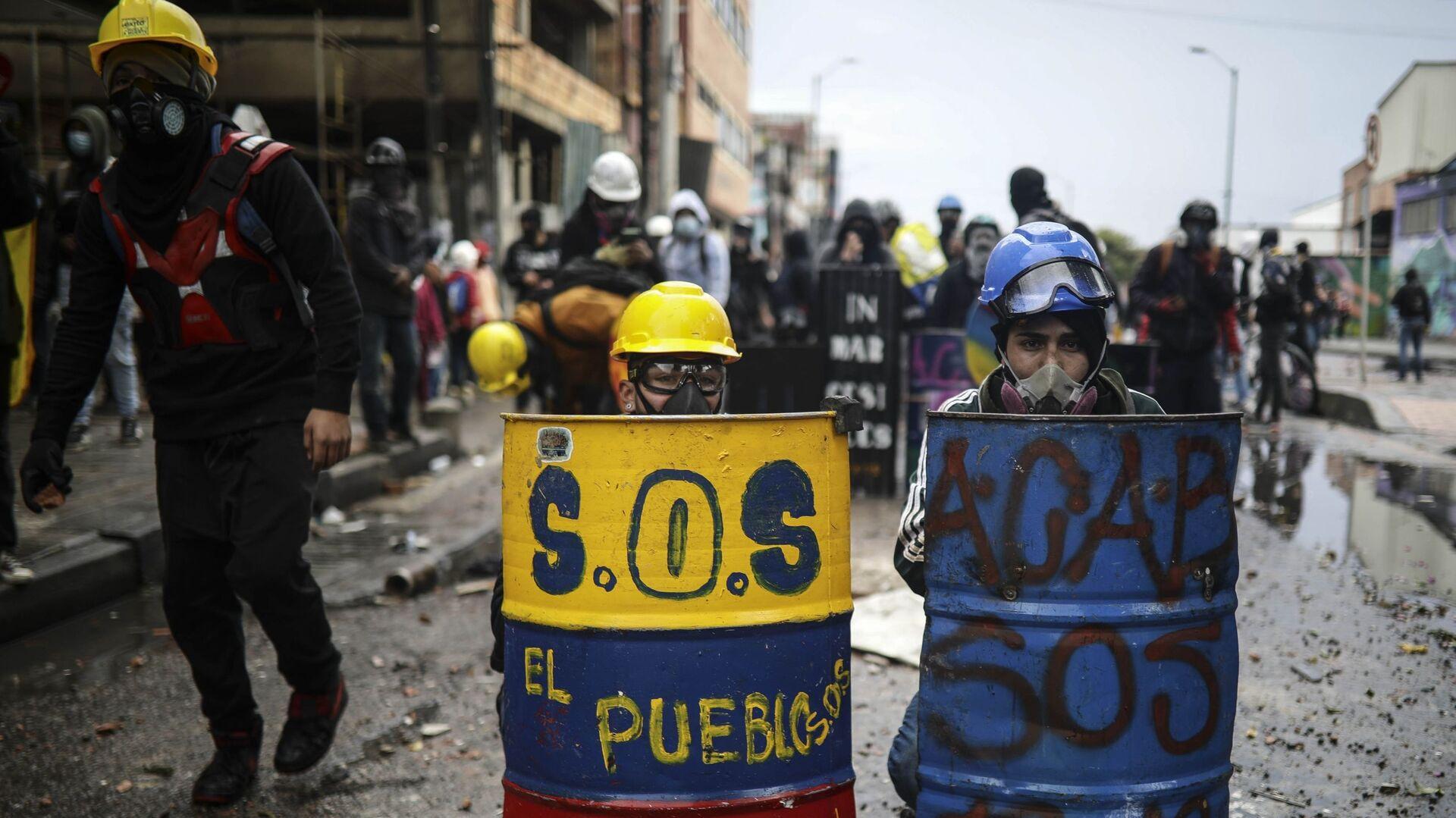 Антиправительственные протестующие прячутся за импровизированными щитами во время столкновений с полицией в Боготе, Колумбия - Sputnik Mundo, 1920, 19.07.2021