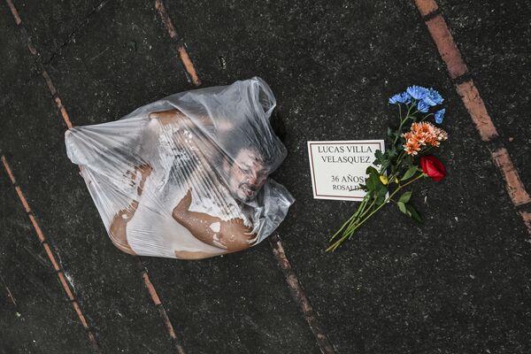 Un hombre posa dentro de una bolsa plástica durante un acto conmemorativo a las víctimas de la violencia policial en las protestas antigubernamentales en Medellín, Colombia. - Sputnik Mundo
