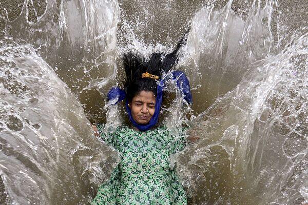 Una niña permanece en una calle inundada tras una fuerte lluvia monzónica en Bombay, la India. - Sputnik Mundo
