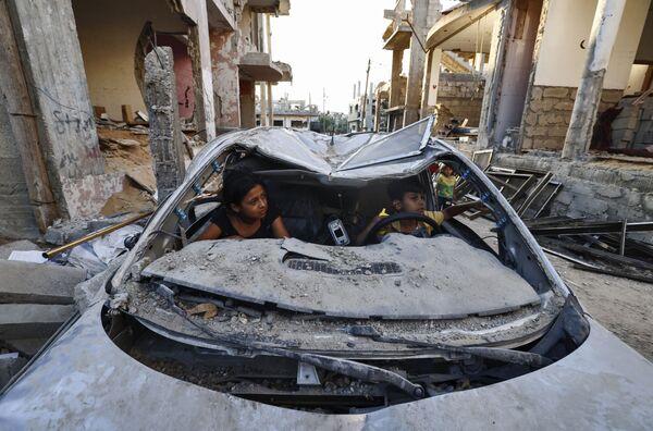 Dos niños palestinos juegan dentro de un coche dañado por los ataques aéreos israelíes en Beit Hanun, Franja de Gaza. - Sputnik Mundo