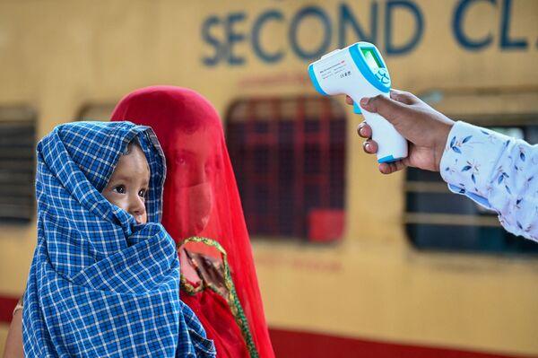 Un trabajador sanitario le toma la temperatura a una pasajera con un bebé en una estación de tren de Bombay, la India. - Sputnik Mundo