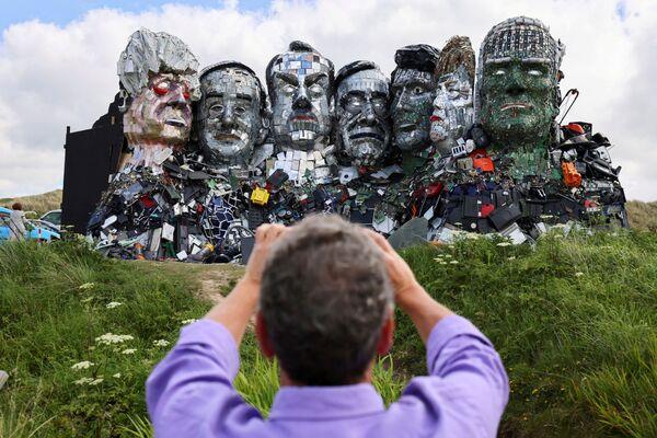 Un hombre fotografía una escultura hecha con residuos tecnológicos, denominada 'Mount Recyclemore', instalada en vísperas de la cumbre del G7 en Hayle Towans, Reino Unido. - Sputnik Mundo
